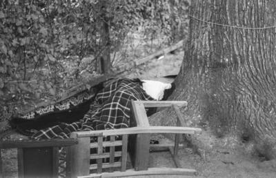 [Primer plano de persona durmiendo tapada con una manta junto a un árbol en los jardines de la Embajada Alemana de Madrid tras el estallido de la Guerra Civil]
