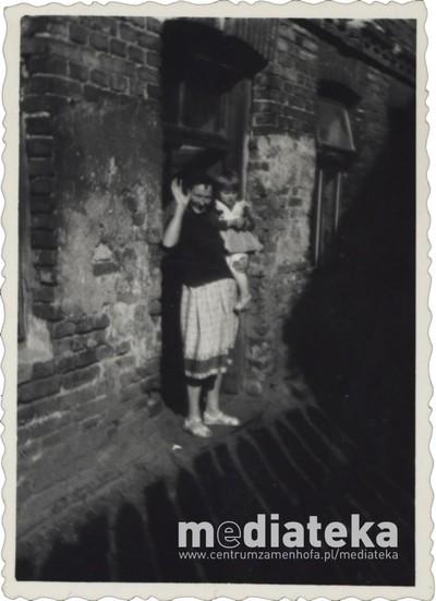 Kobieta z dzieckiem przed domem, ul. Starobojarska 5, Białystok, lata 60. XX w.