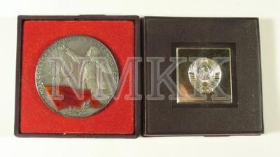 <em>Medaļa, metāla, gar malu teksts krievu valodā, kreisajāpusē cipars 50, labajā pusē V.Ļeņins ar paceltu roku, apakšā sarkans karogs ar sirpi un āmuru un lauru zars.</em> <em>Medaļa atrodas kastītē.</em>