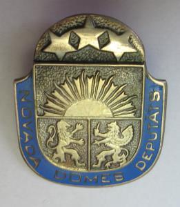 Vairoga forma.Centrā Latvijas mazais ģērbonis, puslokā uzraksts uz zila fona NOVADA DOMES DEPUTĀTS>