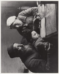 Wolf Nachowicz, the gravedigger, teaching his grandson, whose father is in the U.S.A, to read, while the grandmother looks on