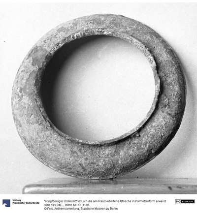 Ringförmiger Untersatz (Durch die am Rand erhaltene Attasche in Palmettenform erweist sich das Objekt als Teil eines Siebs)