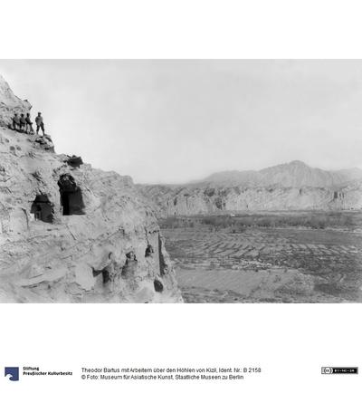 Theodor Bartus mit Arbeitern über den Höhlen von Kizil