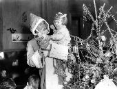Christmas Cheer from America for bombed and evacuated London children.  Children at the WVS Nursery at Hanover Lodge, Regent's Park who are waiting to be evacuated to nurseries in the country, received their Christmas gifts at a party at which Mr Bernard Carter, the American Red Cross delegate in Great Britain, acted as Father Christmas.  Mr Bernard Carter with a happy little girl after she received her gift. 20th December 1941