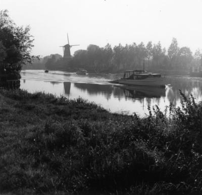 Recreatiegebied. Een boot vaart over het water, op de achtergrond een molen