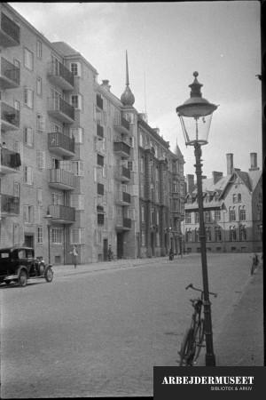 København, Christianshavn(?), bygning med balkoner, et ældre hus ligger i baggrunden