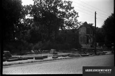 Nedrivning af et gammelt hus i Glostrup, muligvis til Vilh. Lauritzens Rådhus, fortov