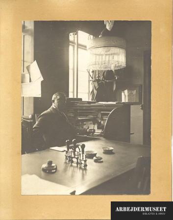 Interiør fra et kontor med en person ved chatollet, og stempler på bordet i forgrunden