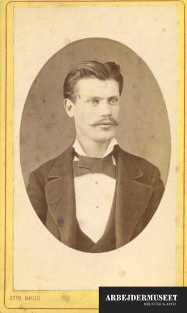 Portræt af mand med overskæg, iført jakke og butterfly
