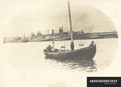 Havneareal med skibe ved kajerne og en mindre båd i vandet, set fra søsiden
