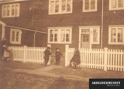 Toetagers træhus med hvidt stakit og legende børn foran
