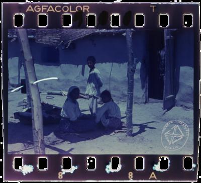 Femeie și copii de țigani rudari, stând în fața casei sub un șopron