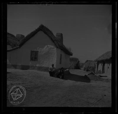 Femeie cu furca de tors, în fața casei