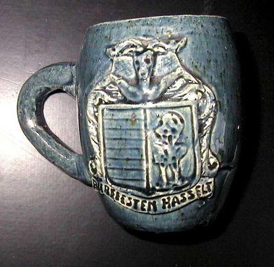 Anoniem, mok met afbeelding van het wapenschild van Hasselt en een bandenrol waarop staat Bierfeesten Hasselt, s.d., blauw geglazuurd keramiek.