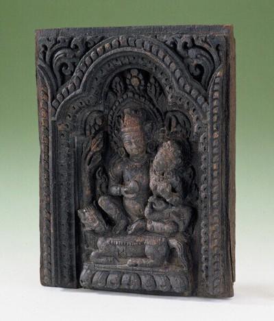 Houtsculptuur met in diep relief gesneden een voorstelling van de god Jambhala, zittende in lalitasana met zijn sakti op een paard. Hij heeft in zijn rechterhand een citroen en in de linkerhand de juwelen spugende mongoose.
