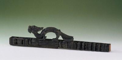 Houten stijl (van een deur of venster), voorzien van een decoratieve draak.