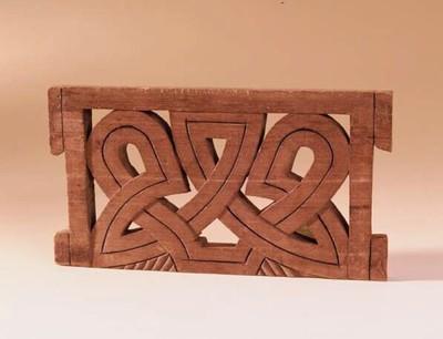 Een uitgesneden houten plank. Rechthoekig met brede houten randen. Op de hoeken zijn eextra blokjes uitgesneden. De binnenkant bestaat uit hout gesneden, brede ( 2,5 cm. ), in elkaar lopende lijnen met een donkere ingekerfde middellijn, daartussen zijn openingen. De figuren zijn elkaars spiegelbeeld. Aan de onderkant zijn nog schuine inkervingen gemaakt.