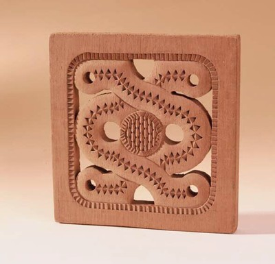 Vierkant houten plank. Heeft een gekartelde omranding. Binnenstuk is regelmatig uitgesneden, waarin in de hoeken gaten geboord zijn. Verder in het midden boven en onder 2 gaten uitgeboord. Middenin is een ring geschubd uitgesneden. In een soort slangvorm is een lint van ruitjes uitgesneden. Achitectonische versiering. Mechanisch gemaakt.