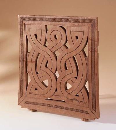 Een uitgesneden houten plank. De houten plank heeft een brede rand ( 4 cm. ) waarin in het midden een strook van ruitjes is uitgesneden. Aan 3 kanten loopt de rand in elkaar over. De onderkant staat op zich. de binnenkant wordt gevormd door brede, uit hout gesneden in elkaar kronkelende lijnen ( 4 cm. ) met daartussen openingen. Versierd met een donkere ingekerfde middellijn. De delen van de binnenkant zijn elkaars spiegelbeeld. Aan de beide zijkanten is een smalle gebogen strook van horizontaal ingesneden lijntjes. De onderkant van de plank is 2 cm. breder dan de bovenkant. Aan de 2 hoeken zit een inkeping met daaronder 2 ruitvormige stukjes hout.