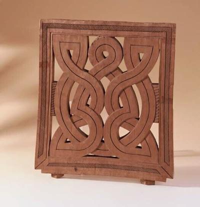 ( Dit voorwerp is identiek aan dat van nummer 201537 ). Een uitgesneden houten plank. De houten plank heeft een brede rand ( 4 cm. ) waarin in het midden een strook van ruitjes is uitgesneden. Aan 3 kanten loopt de rand in elkaar over. De onderkant staat op zich. de binnenkant wordt gevormd door brede, uit hout gesneden in elkaar kronkelende lijnen ( 4 cm. ) met daartussen opningen. Versierd met een donkere ingekerfde middellijn. De delen van de binnenkant zijn elkaars spiegelbeeld. Aan de beide zijkanten is een smalle gebogen strook van horizontaal ingesneden lijntjes. De onderkant van de plank is 2 cm. breder dan de bovenkant. Aan de 2 hoeken zit een inkeping met daaronder 2 ruitvormige stukjes hout.