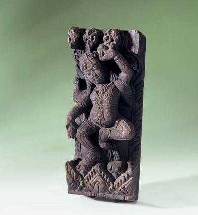 Houtsculptuur voorstellende een dansende figuur met voorwerpen in de handen.