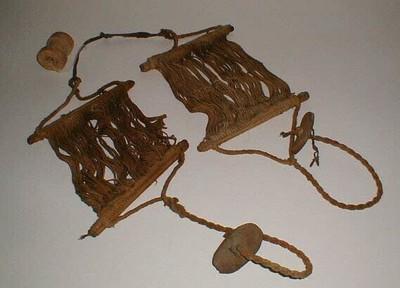2 schachten van een weefgetouw. De schachten zijn aan elkaar gebonden met een donkerbruin leren bandje. Aan elke schacht een getwijnd koordje waaraan een plat stukje hout, dat (tussen de tenen van de wever geklemd), de schachten gespannen hout. Los erbij een houten katrolletje, grof gesneden.