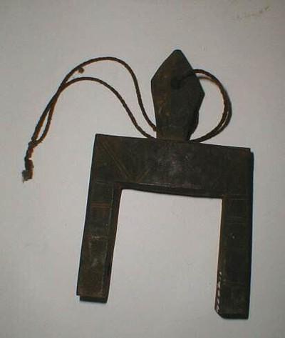 Weefkatrolhouder van hout met op de voor- en achterkant van de vork ingekerfde zigzag- en horizontale lijnen. De as en de katrol ontbreken. Bovenop de vork zit een ruitvormig 'handvat' met een gaatje waardoorheen een touwtje zit.