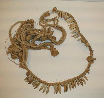 Zeer lange, gevlochten katoenen band, met in het midden een 50 cm lange rij van aaneengeregen tanden die bijgeslepen zijn.