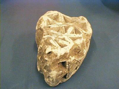 Een bewerkt stuk steen, mogelijk een fragment van een boog. De versiering bestaat uit diep uitgestoken driehoeken, voornamelijk aan de beide zijkanten. De bovenkant maakt de indruk onvoltooid te zijn.