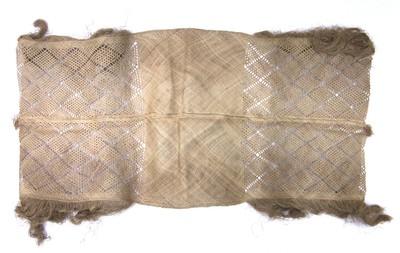 Weefsel is in drie delen verdeeld, het middelste deel is dicht gevlochten. De twee zijstukken zijn grof gevlochten in ruitpatroon. Aan de twee zijstukken zit aan beide kanten franje en over de gehele lengte zit een naad in het midden. Hier is het weefsel aan elkaar gevlochten in visgraatmotief. Aan de uiteinden zit een klein kwastje. Kokos, cremekleurig.