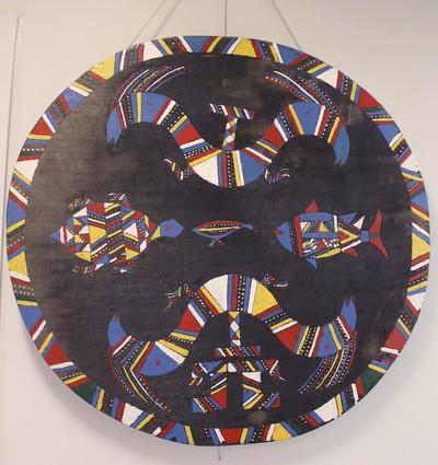 Forse cirkelvormige houten nokversiering. Op het zwarte fond zijn veelkleurige, deels ingekerfde, afbeeldingen aangebracht van mythische dieren: een 2-koppige rupsgeest (ëlukë), een schildpad (kuliputpë) en een vis (een watau) en in het midden een hokko, een wilde hoendersoort.
