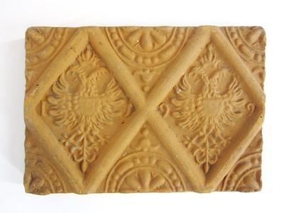 Een siertegel waarop binnen ruitvormige kaders een florale decoratie in reliëf is aangebracht.