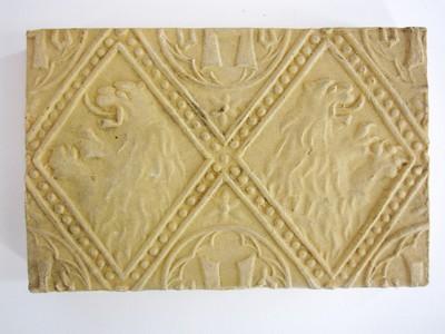 Een siertegel waarop binnen ruitvormige kaders decoraties in reliëf zijn aangebracht waaronder twee klimmende leeuwen vanaf de torso zijn afgebeeld.