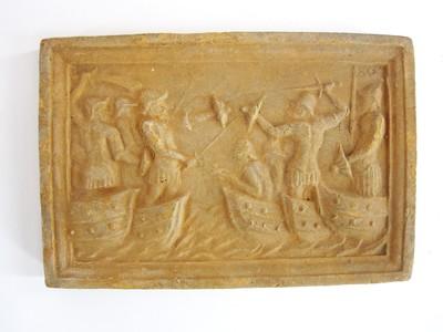 Een siertegel waarop binnen een rechthoekig kader in reliëf een oorlogstafereel van een gevecht tussen mannen in boten is afgebeeld.