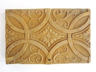 Een siertegel waarop in reliëf een geometrische en florale decoraties zijn is aangebracht.