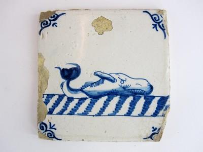 Een Delftsblauwe tegel met op een witte ondergrond blauw aangebrachte voorstelling van een potvis. In de hoeken zijn florale motieven aangebracht.
