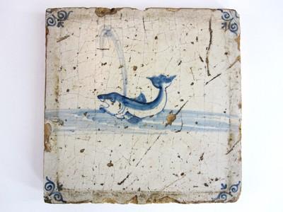 Een Delftsblauwe tegel met op een witte ondergrond blauw aangebrachte voorstelling van een spuitende potvis.