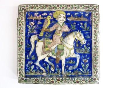 Een geglazuurde tegel uit Iran met een polychrome beschildering. Op de tegel is een ruiter met een valk afgebeeld tegen een blauwe achtergrond met bloemen. Het geheel is gevat in een wit kader eveneens versierd met bloemen. In paleizen en woonhuizen van welgestelden was vaak een fries aangebracht bestaande uit een rand van dergelijke tegels. Het betreft hier een moderne reproductie uit de Qajar periode van een traditioneel gegeven. Jachttaferelen zoals deze verwijzen vaak naar een oud jachtverhaal over de held Rustam uit Firdausi's Boek der Koningen.