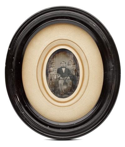 Een daguerreotypie van een vader met vier kinderen in de originele ovale lijst.