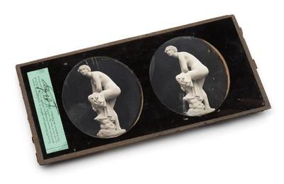 Een stereo daguerreotypie ingelijst achter een glasplaatje. Op de afbeelding is een mamerbeeld te zien.