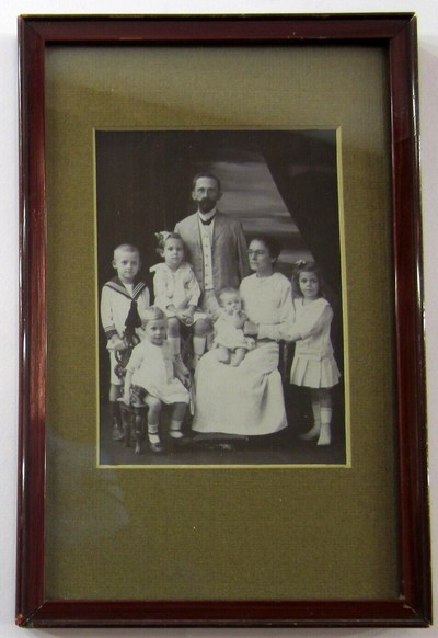 Twee ingelijste fotopositieven: a) een familieportret gemaakt in 1918 in Nederlands-Indië. Het meisje rechts op de foto is in 1919 op 5-jarige leeftijd overleden tijdens de bootreis naar Nederland. Naar aanleiding hiervan heeft de familie in Den Haag met als basis het familieportret een los portret van het meisje laten maken. b) het portret van het overleden meisje. Op de achterzijde: