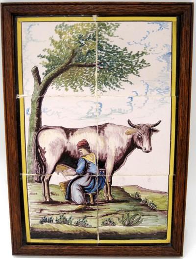 Een tableau van zes tegels gevat in een houten lijst. Op de tegels is een gekleurde afbeelding aangebracht van een vrouw die onder een boom een koe aan het melken is.