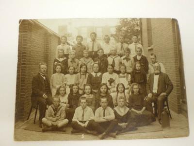 Een foto van een groep jongens en meisjes poserend op een binnenplaats. Aan weerszijde van de groep kinderen zit een volwassen man, vermoedelijk de leerkracht. In een bijgevoegd briefje van de schenkster blijkt, dat dit de school is van haar moeder. De school staat/stond (?) in de Amsterdamse Lepelstraat.