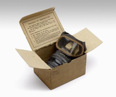 Zwart rubberen gasmasker voor kinderen van engels fabrikaat (typenr. WWM 0304). Het is voorzien van witte katoenen hoofdbanden die met metalen gespjes aan het masker vastzitten. Aan het masker zit een filter van hard groen gekleurd metaal dat met een zwarte tape aan de rest van de filterbus zit. Het masker zit in een bruine kartonnen doos met in het deksel in het Engels de gebruiksaanwijzing