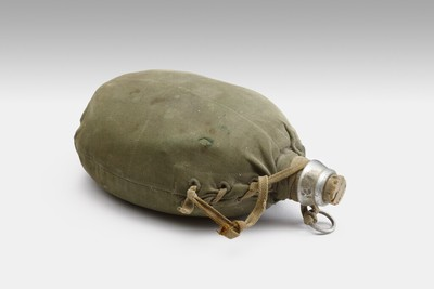 Veldfles (aluminium?) in een groene linnen zak. Deze is vast gebonden - rond de hals - met een bruin veterkoord, eventueel dienst doende als handvat of ophangkoord. De stop van de veldfles is een bruine kurk.