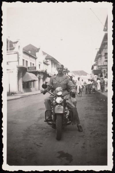 Militairen op een motor en bij een auto