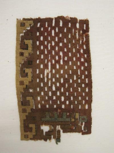 Grafgift. Een weefselfragment van katoen en wol met de kleuren oker, bruin, rood, groen en zwart. Weeftechniek: kelim. Op het fragment geometrische figuren. In het middelste gedeelte zijn bij het weven vierkantjes opengelaten. De linkerkant heeft een okerkleurige band van blokmotieven. Aan de onderkant een groen geometrisch figuur.