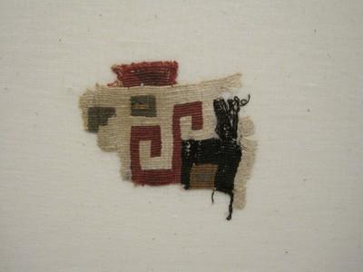 Grafgift. Een weefselfragment waarvan de kettingdraden van katoen zijn en de inslagdraden van wol (waarschijnlijk van een lam of alpaca). Weeftechniek: kelim. De ondergrond is wit met daarop een blokmotief in de kleuren zwart, rood, geel en groen.