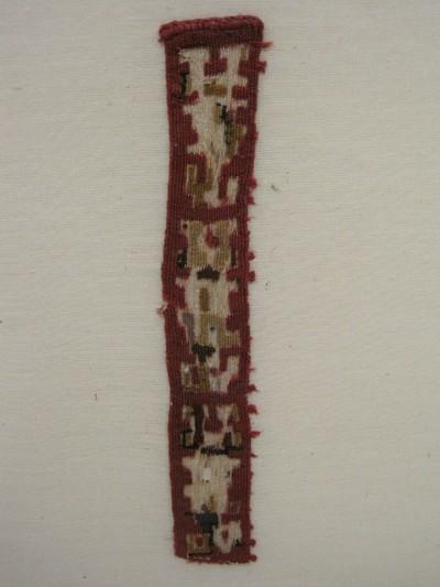 Grafgift. Een weefselfragment van wol met de kleuren rood, blauw en geel. Weeftechniek: kelim. De blokmotieven zijn vergaan en alleen het rode kader is intact. Deze motieven waren waarschijnlijk in verschillende kleuren uitgevoerd. Het fragment bestaat uit drie stukken met daarin H-vormige patronen.