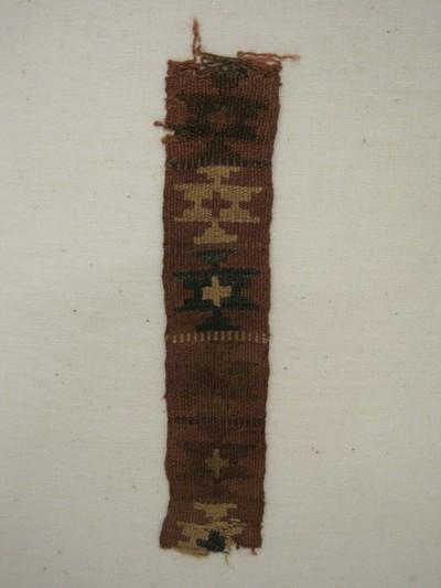 Grafgift. Een weefselfragment van wol en katoen dat waarschijnlijk een deel van een slinger of centuur was. Met de kleuren oker, rood, bruin en zwart. Weeftechniek: kelim. Geometrische figuren met in de kern een kruis.